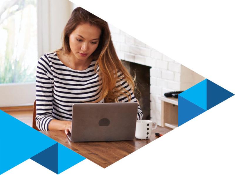 seorang wanita mengenakan baju belang belang sedang menggunakan laptop di atas meja, cangkir putih