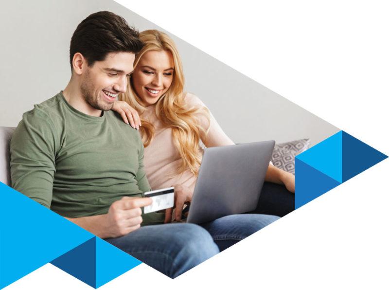 pasangan yang sedang menggunakan laptop di atas sofa, pria memegang kartu kredit