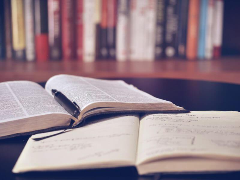 gambar buku yang sedang terbuka dengan pulpen di atasnya, terdapat beberapa buku di depannya juga
