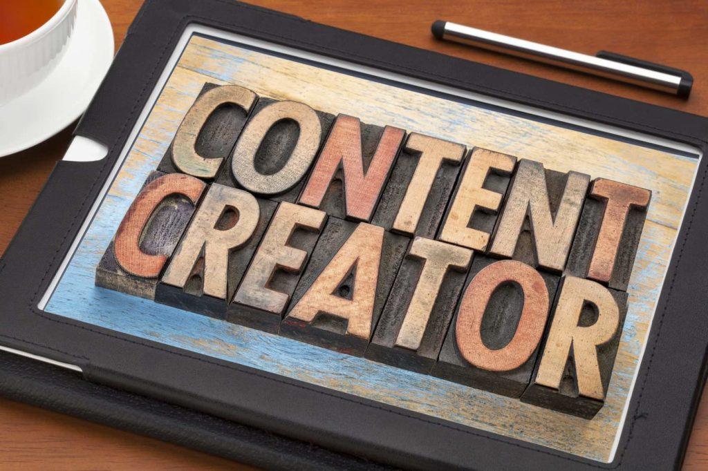 Gambar tulisan content creator di tablet berada di atas meja kayu beserta secangkir teh dan pulpen