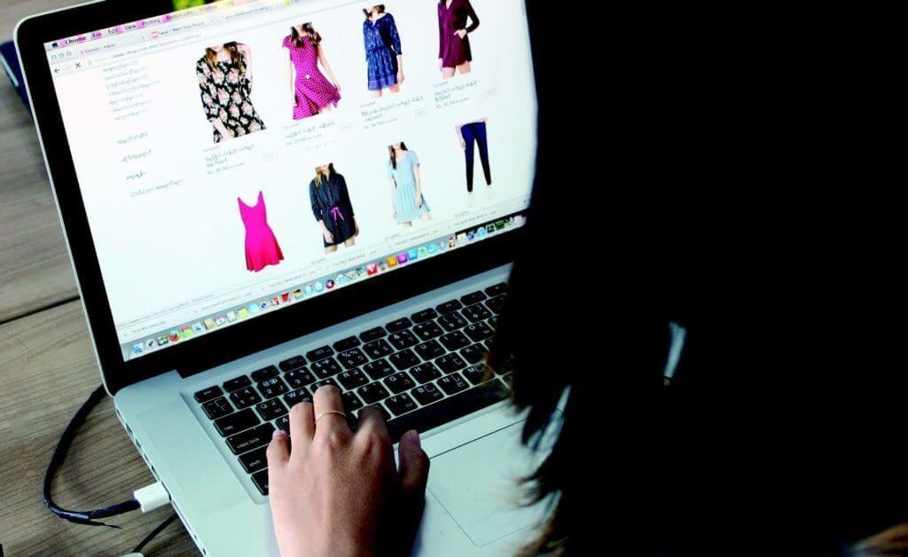 seorang perempuan yang sedang menggunakan laptop untuk berbelanja online