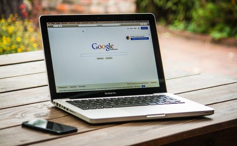 macbook pro di atas meja kayu dengan smartphone di sampingnya