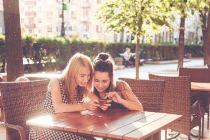 dua wanita sedang duduk sambil melihat smartphone