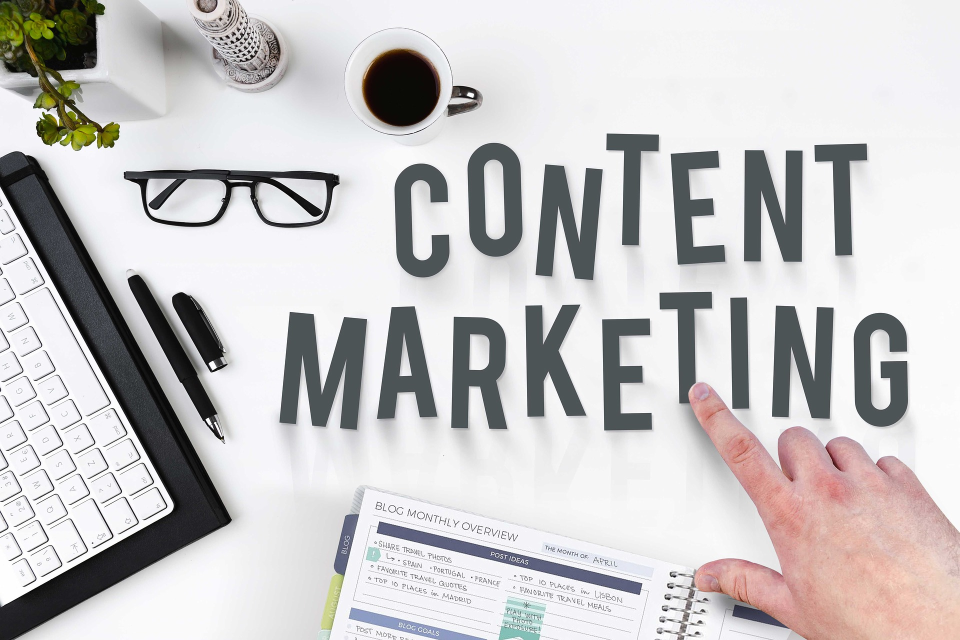 tulisan content marketing di atas meja dengan background warna putih, kaca mata, segelas kopi, keyboard laptop