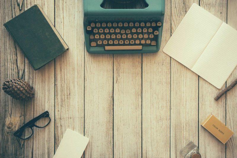 mesin ketik, buku catatan, kacamata, di atas meja kayu